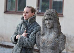 """Linnéa Grimstedt ute på Gotlands Kulturrums gård, intill Lennart Dahlqvists skulptur """"Skiss på ung flicka"""" ."""